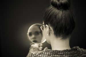 Woman Looking At Self Reflection In Mirror..